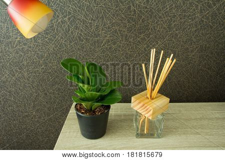 Modern workplace with tree pot and reed freshener on wood table