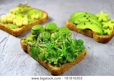 Toast  with  avocado  and micro greens ,banana and kiwi