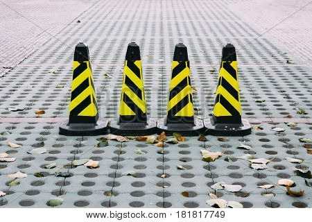 Yellow and black traffic cone on stone road. used for warning to stop