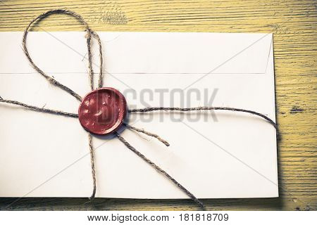 Old letter envelope with wax seal on wooden surface