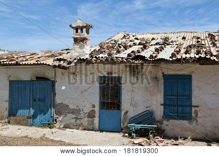 Derelict house with blue door on Crete Greece
