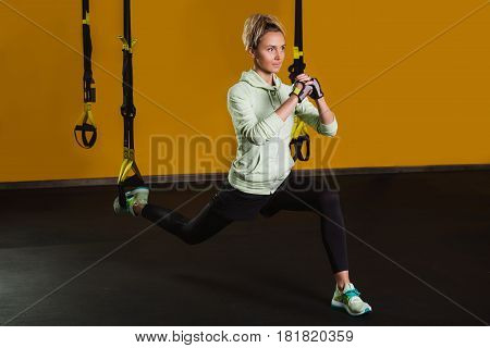 Sporty woman doing lunge using suspension straps, at gym. Suspension training for slim body. Exercises for beautiful legs