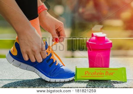 woman getting ready for fitness workout outdoors, lacing running shoes near sports nutrition. Sports training on a sunny day