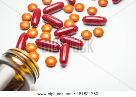 Supplementary food vitamin medicine orange pills or red capsules spilled from a glass bottle.