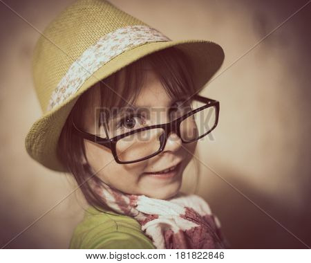Fashionable little girl looks slyly from under his glasses.