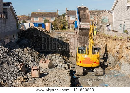 Excavator is digging a house foundation in a residential area while a dumper truck is unloading construction gravel sand and crushed stones on the construction site.