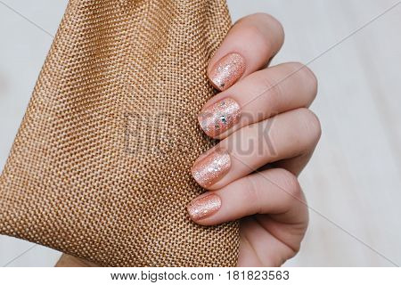 Beautiful female hand with beige glitter nail design.