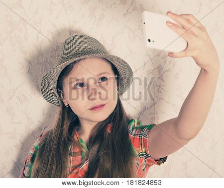 Happy young girl looks in her smartphone and photographed.