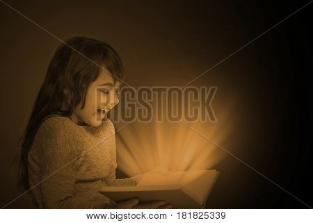 Vintage dark photo of smiling long haired little girl holding open book in her hands. From the book emerge dark yellow rays that dazzle the gir`s face. All is on the dark background.