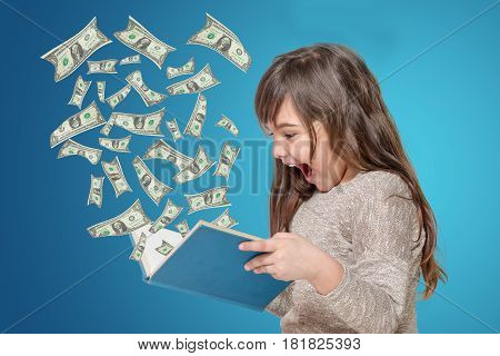 Surprised long haired little girl holding open book in her hands. From the book flies off the US dollar bills All is on the blue gradient background.