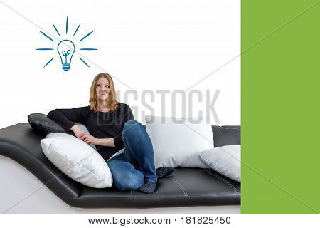Grinning long haired young woman is sitting on a black and white couch with black and white pillows. Woman is looking upwards on the illustration of a lit bulb in the background. Empty trendy green color rectangle is ready for your text.
