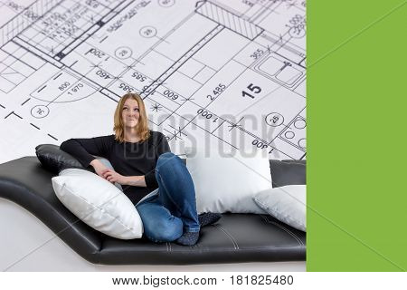 Grinning long haired young woman is sitting on a black and white couch with black and white pillows. Woman is looking upwards on the interior house plan in the background. Empty trendy green color rectangle is ready for your text.