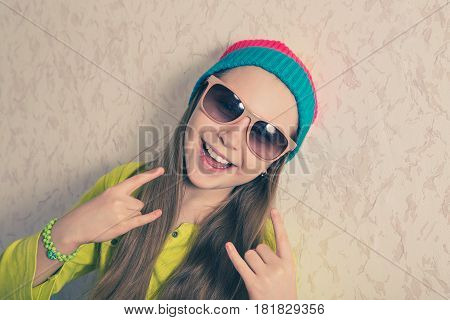 A young girl in a knitted cap and sunglasses near the wall.