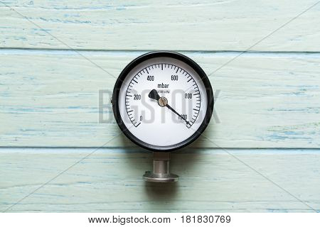 pressure gauge on wood background, top view
