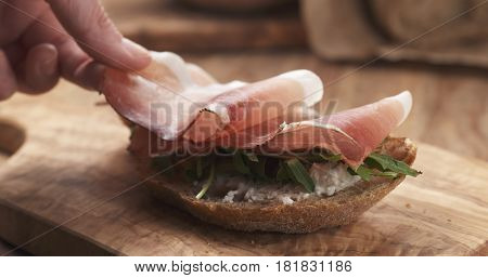 italian speck put on rustic bread with arugula and ricotta cheese, 4k photo