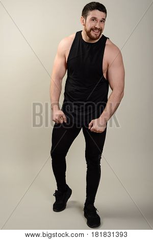 Confident willing young athletic man in sportswear looking at camera. Full body length portrait over white studio background.