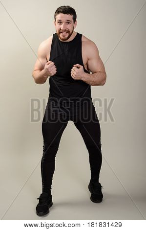 Severe bearded middle-aged fighter is in a frontal protective pose against a gray background.
