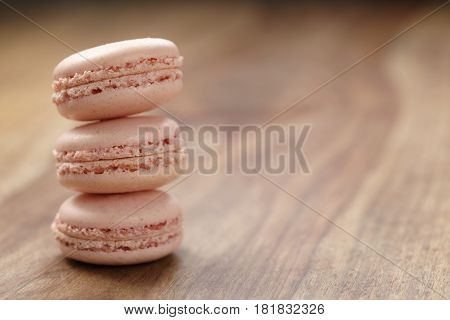 closeup shot stack of pastel colored macarons with rose flavour on wood table, copy space