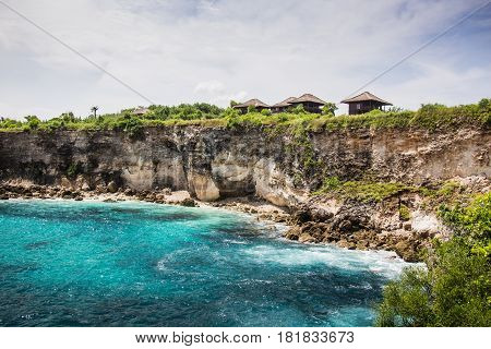 View of clear blue lagoon and cliff side with huts in the distance. Ceningan Island, Bali.