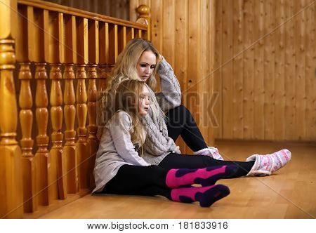 parent with child sitting on the floor near the wooden staircase railing