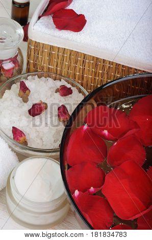 Accessories for manicure: hand bath with rose petals, essentials oils,  bath salt, towels, cream. Close-up. Beauty and spa concept