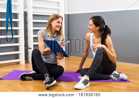Young woman and her fitness instructor are having conversation at the gym about exercising.