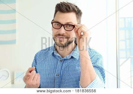 Young man with contact lens at home