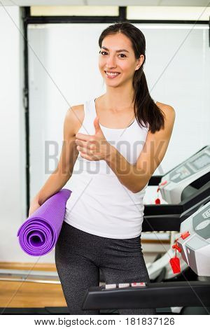 Beautiful fitness woman exercising and showing thumb up at the gym.