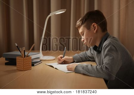 Incorrect posture concept. Schoolboy sitting at table in room
