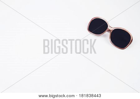 A pair of pink sunglasses on a white background