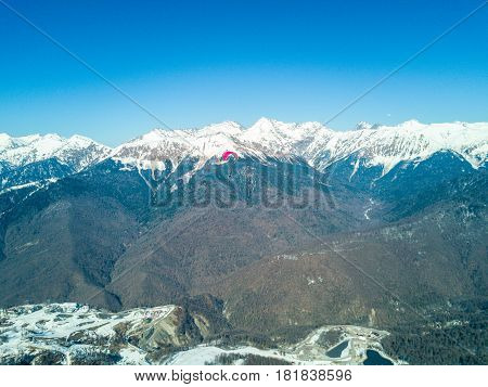 Paraglider flies over the mountains over the ski resort in Rosa Khutor