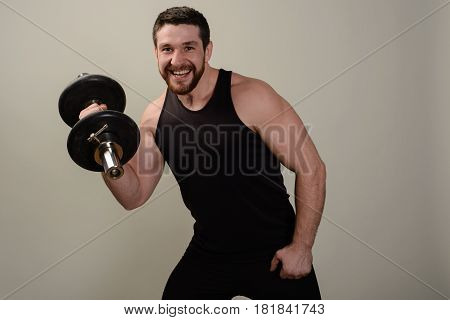 Young Smiling Athlete Performs An Exercise With Dumbbells On The Development Of The Muscles Of The H
