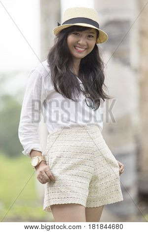 portrait of beautiful street fashion shot of asian younger woman wearing straw hat standing outdoor