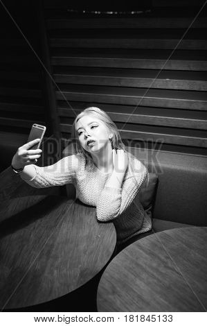 Young Blond Woman In A Knitted Sweater, Making A Selfie Photo On A Smartphone, Sitting At A Table In