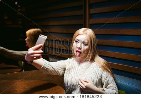 Young Blond Woman In A Knitted Sweater, Making A Selfie Photo On A Smartphone Emotionally Shows Tong