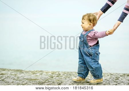 Cute baby girl walking on the promenade by the sea holding hands mother. Alushta, Crimea.