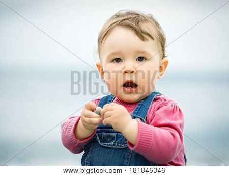 Cute one-year child playing with pebbles on the beach. Baby opened his mouth.