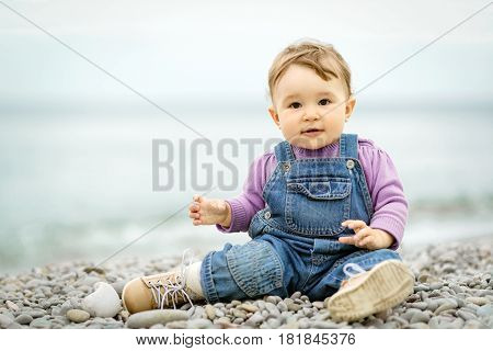 Happy one-year old child playing with pebbles on the sea beach
