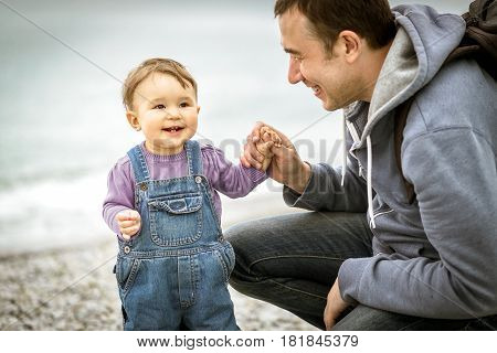 Happy father and one-year child playing on the beach. Father holding baby's hand.