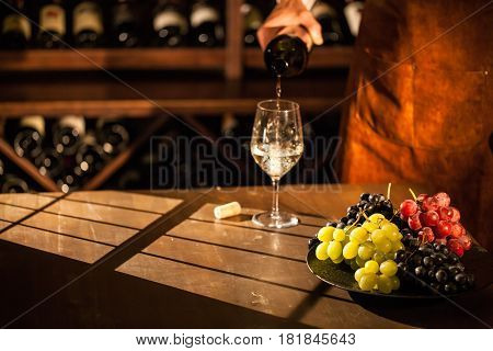 Sommelier pouring wine into a glass. Glass standing next to plate with fruits. Wine vault location.