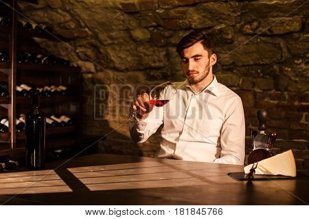 Handsome young man sitting by the table in a wine vault and holding a glass of wine in his hands.