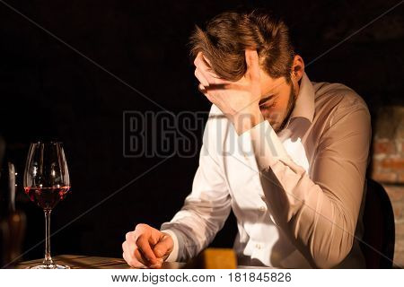 Handsome man sitting by the table leaning his haed on his hand. Glass of wine placed near the man.