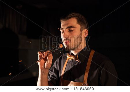 Handsome man blowing on a hookah ember.