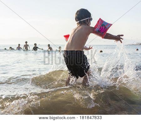 Little cute boy splashing in the sea water