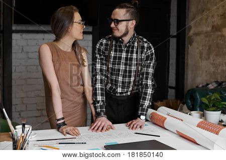 Couple in love look each other on the work. Colleagues discussing ideas and plans for holidays. Stylish man and woman start relations in job time. Male hold female hand and feel hot.
