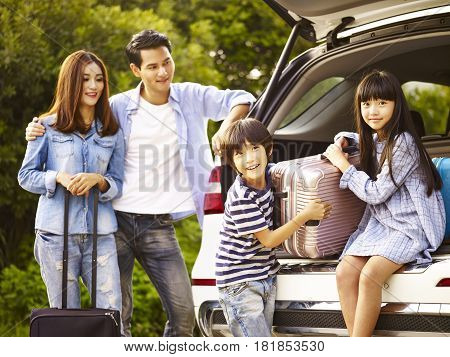 cute asian children helping unloading luggage from trunk while parents watching affectionately.