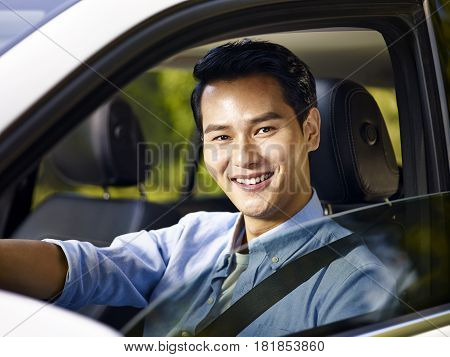 young asian adult man sitting in a car with safety belt on looking at camera smiling.