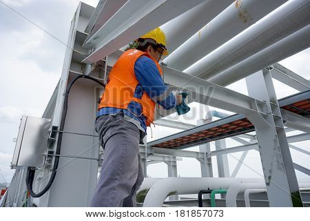 A Male Worker Doing A Maintenance Work By Cleaning And Inspecting An Explosion Proof Security Camera
