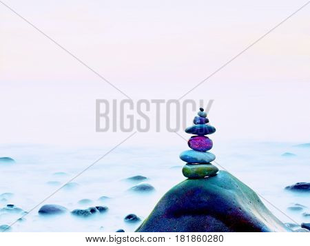 Stacked Rounded Stones At Sea. Polished Pebbles On Dark Wet Rock,  Smooth Water