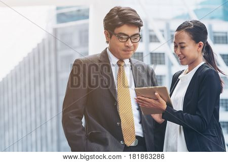 Businessman And Businesswoman Discussion With Tablet